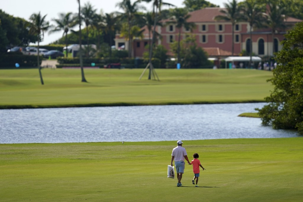 A man and child walk along the course during a practice day for the Walker Cup golf tournament at Seminole Golf Club in Juno Beach, Fla., Friday, May ...