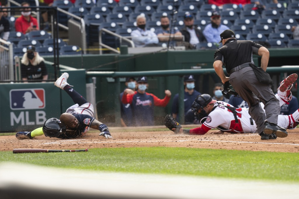 Atlanta Braves' Marcell Ozuna, left, slides safely into home as Washington Nationals' catcher Yan Gomes (10) tries a tag during the fourth inning of a...