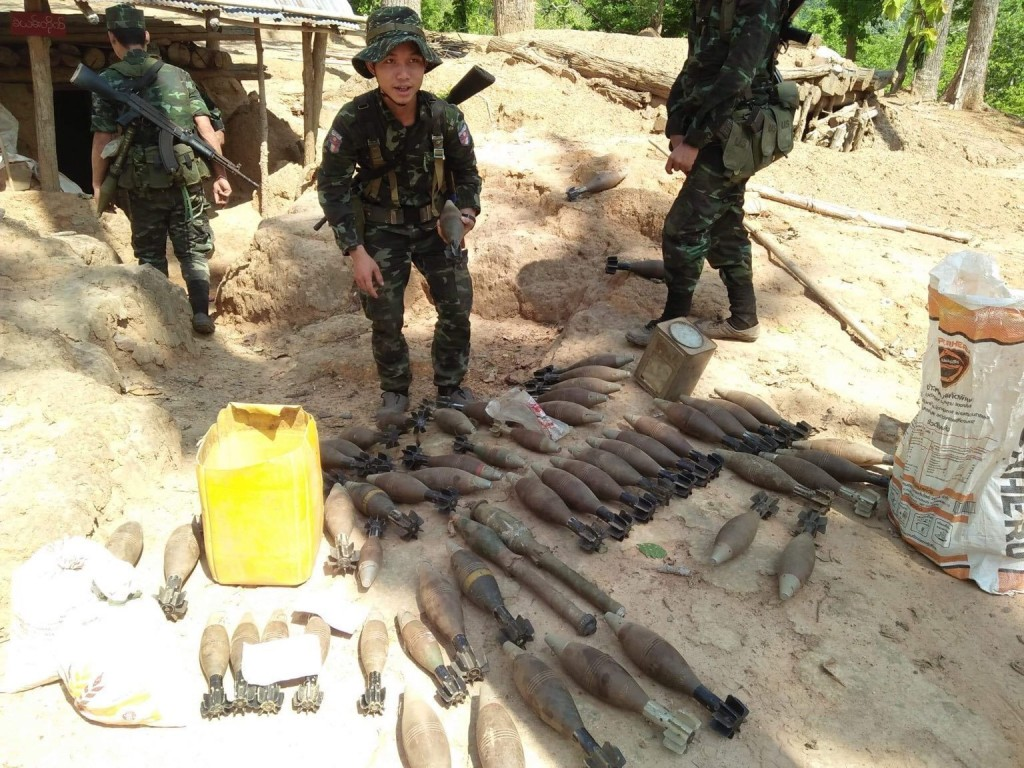 In this photo provided by Karen National Liberation Army, a Karen National Liberation Army soldier holds a motor shell while standing next to a cache ...