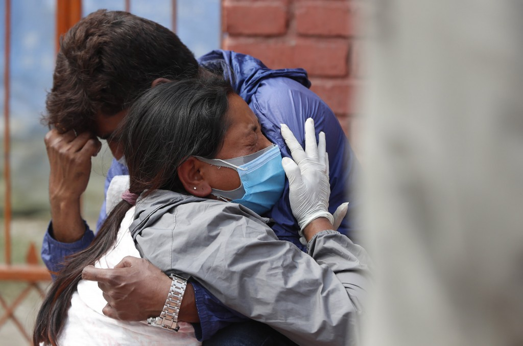 Relatives of a person who died of COVID-19 mourn at a crematorium in Kathmandu, Nepal, Friday, April 30, 2021. An infection surge in Nepal has prompte...