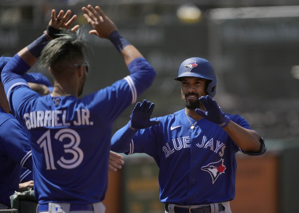 Toronto Blue Jays' Marcus Semien, right, celebrates with Lourdes Gurriel Jr. (13) after hitting a solo home run against the Oakland Athletics during t...