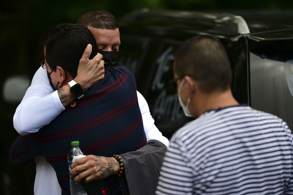 Jose Antonio Rodriguez, left, is embraced by a relative as he arrives at a wake for his 27-year-old-daughter Keishla Rodriguez, whose lifeless body wa...