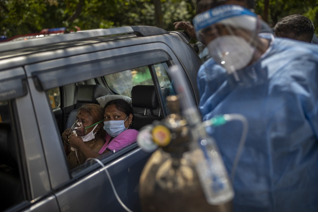 FILE - In this April 24, 2021, file photo, a patient receives oxygen inside a car provided by a Gurdwara, a Sikh place of worship, in New Delhi, India...