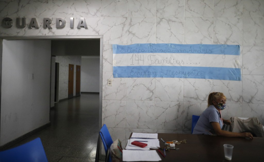 Cleaning worker Maria Sandra Gonzalez sits at the entrance of the San Andres Clinic which has been occupied by its former workers since it closed at t...