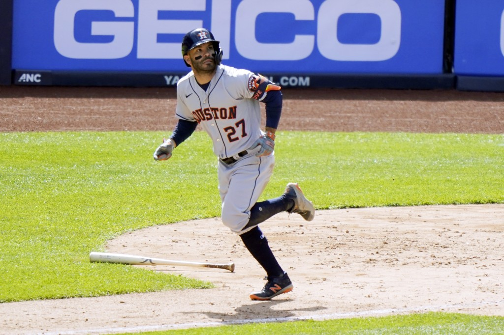 Houston Astros' Jose Altuve (27) watches his eighth-inning, three-run, home run as he trots the base path in a baseball game against the New York Yank...