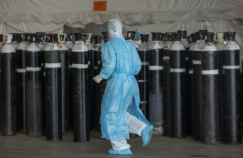 FILE - In this Jan. 11, 2021, file photo, a health worker in a protective suit runs past oxygen cylinders in a makeshift emergency unit for COVID-19 p...
