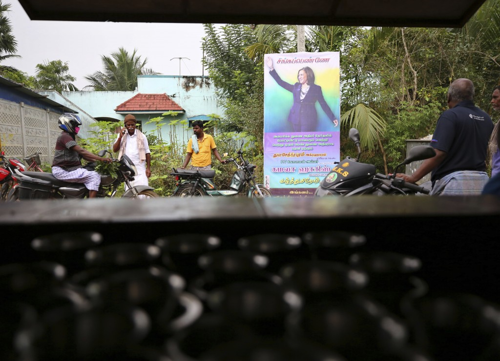 FILE - In this Jan. 20, 2021, file photo, Indian villagers gather outside a local eatery next to a banner featuring Vice President-elect Kamala Harris...