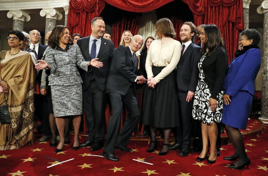 FILE - In this Jan. 3, 2017, file photo, then-Vice President Joe Biden, center, ducks down so all of the family of then-Sen. Kamala Harris, D-Calif., ...