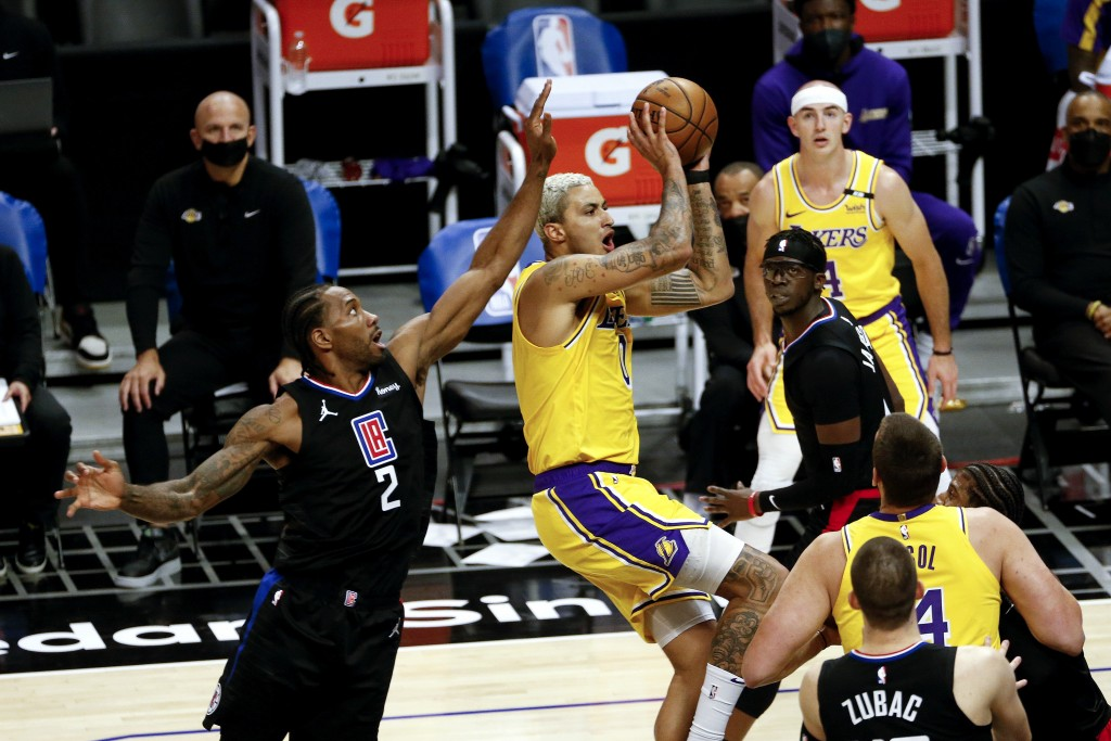 Los Angeles Lakers' Kyle Kuzma shoots under pressure from Los Angeles Clippers' Kawhi Leonard (2) during the first half of an NBA basketball game Thur...