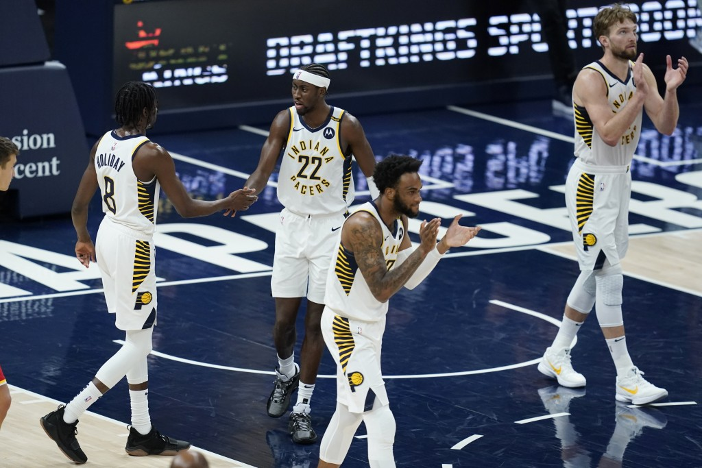 Indiana Pacers' Justin Holiday (8), Caris LeVert (22), Oshae Brissett (12) and Domantas Sabonis (11) celebrate after the Pacers defeated the Atlanta H...