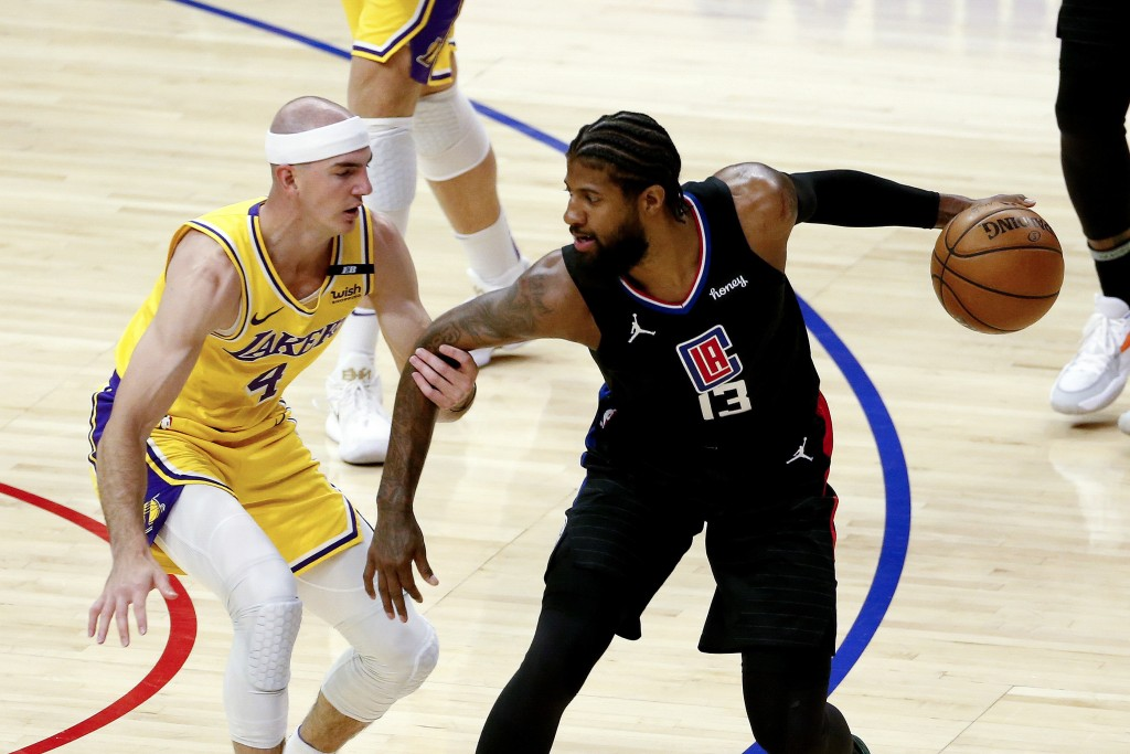 Los Angeles Clippers' Paul George (13) is defended by Los Angeles Lakers' Alex Caruso (4) during the first half of an NBA basketball game Thursday, Ma...