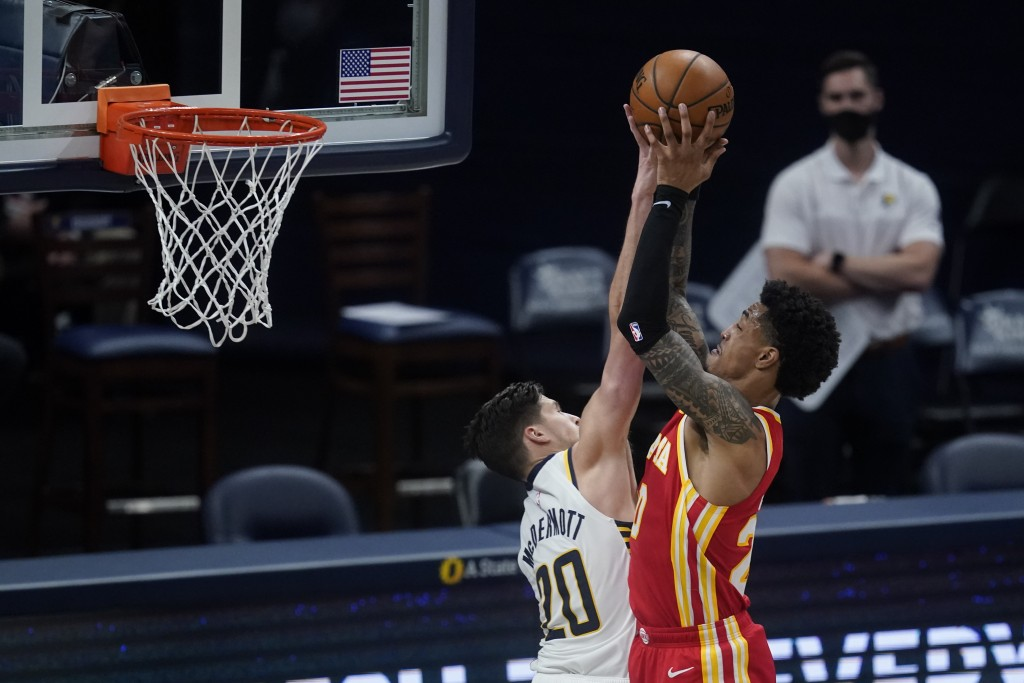 Atlanta Hawks' John Collins, right, is fouled by Indiana Pacers' Doug McDermott during the second half of an NBA basketball game Thursday, May 6, 2021...