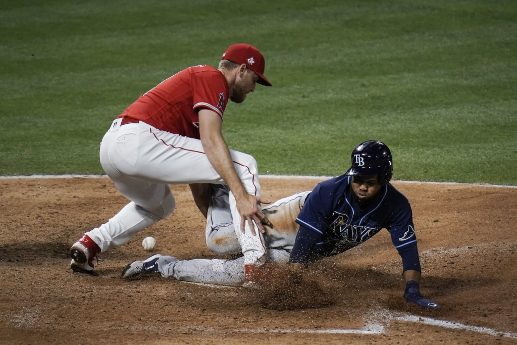 Tampa Bay Rays' Manuel Margot, right, scores as Los Angeles Angels relief pitcher Aaron Slegers misses the throw during the eighth inning of a basebal...