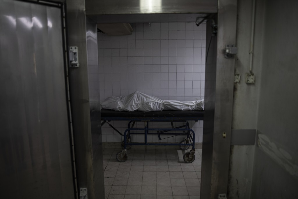 The covered body of a man who died of COVID-19 lies inside a morgue of the Gaza European Hospital in the Gaza Strip, Thursday, May 6, 2021. In the cro...