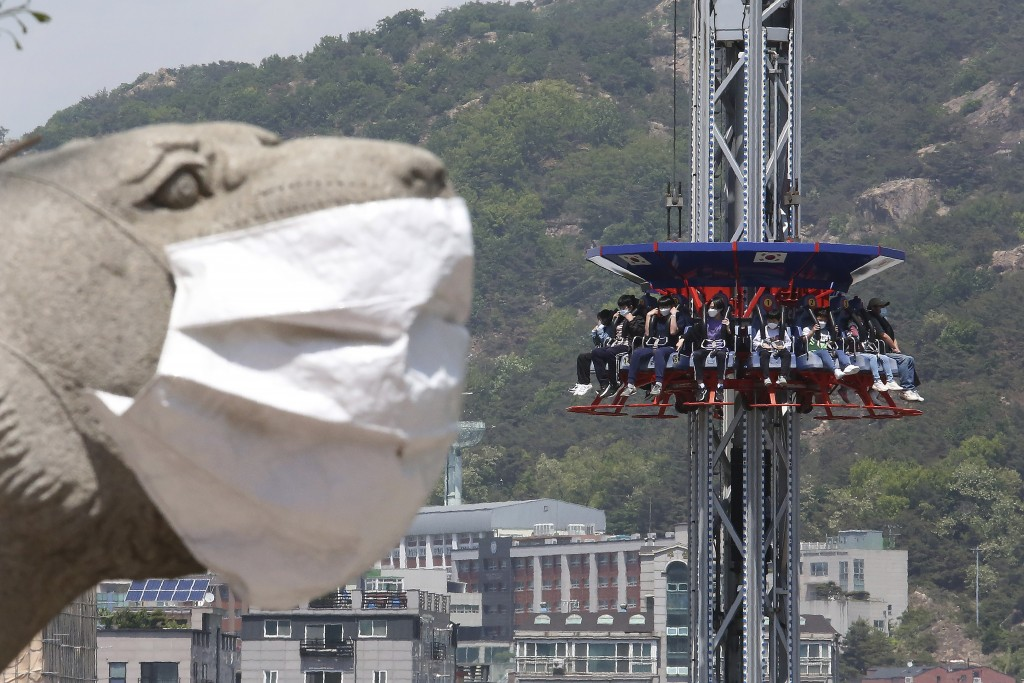 People wearing face masks as a precaution against the coronavirus ride Gyro Drop as they visit to celebrate Children's Day at Children's Grand Park in...