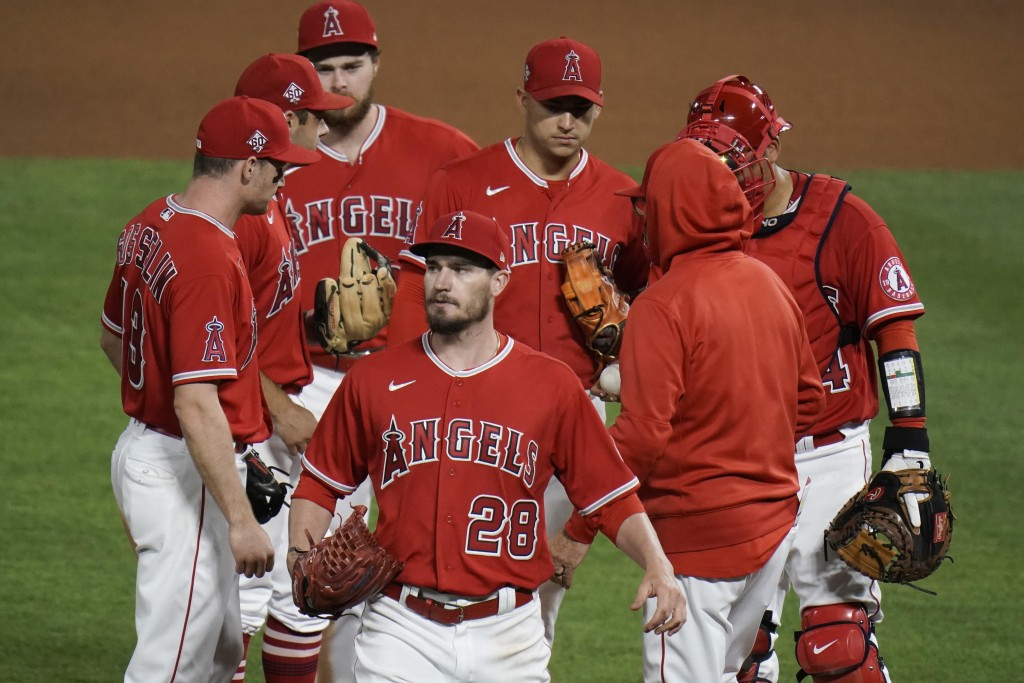 Los Angeles Angels starting pitcher Andrew Heaney, center, leaves the mound and the baseball game during the seventh inning against the Tampa Bay Rays...