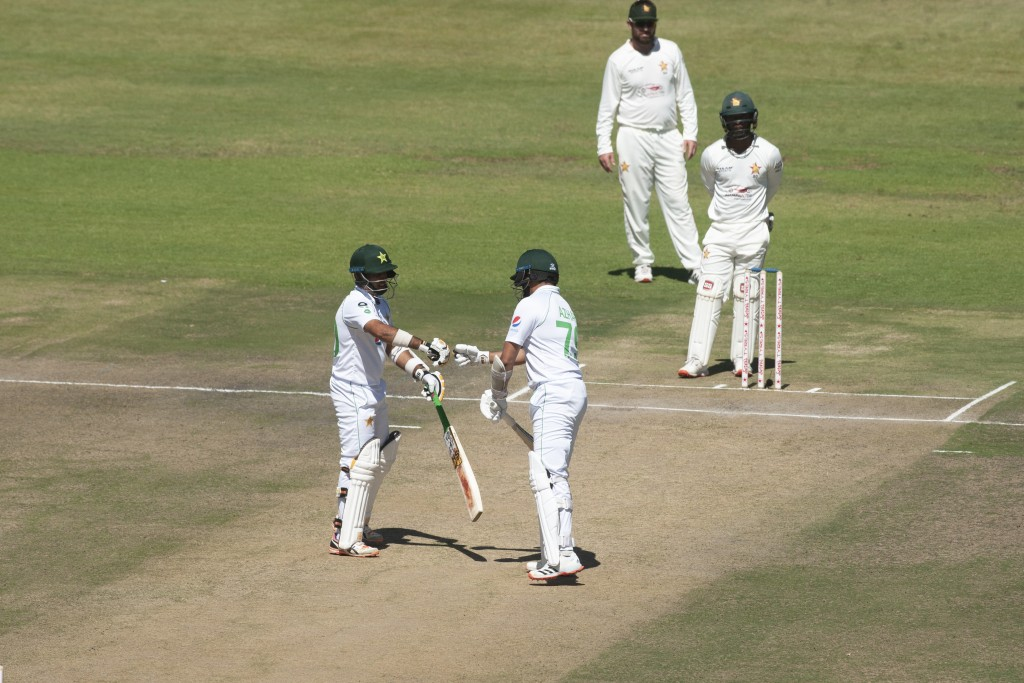 Pakistan batsman Azhar Ali,right, touches gloves with fellow batsman Abid Ali during the second test cricket match against Zimbabwe at Harare Sports C...
