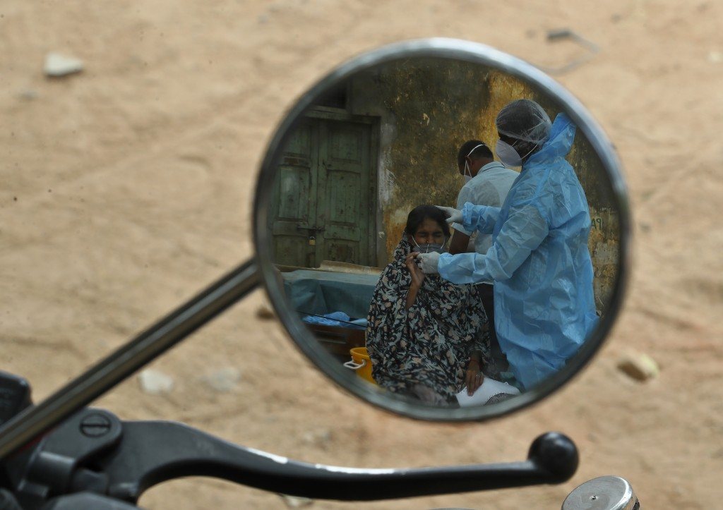 A health worker takes a nasal swab sample of a woman to test for COVID-19 are reflected in a mirror of a motorcycle in Hyderabad, India, Friday, May 7...
