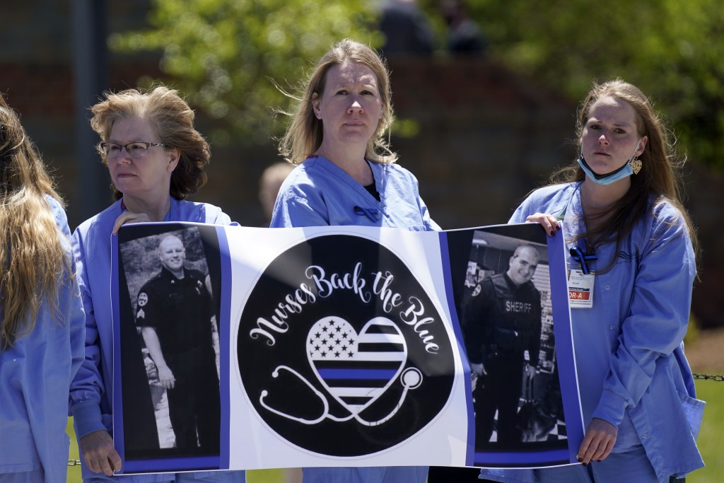 Nurses watch as a processional approaches the Holmes Convocational Center for the funeral services of Watauga County Sheriff's Deputies Sgt. Chris War...