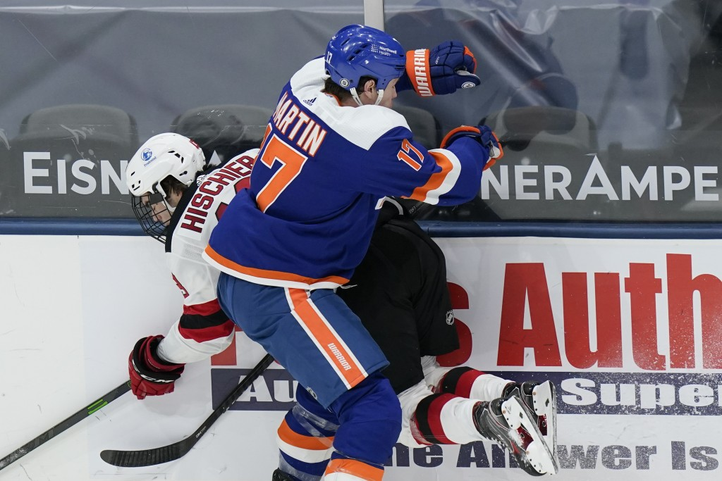 New York Islanders' Matt Martin (17) checks New Jersey Devils' Nico Hischier during the second period of an NHL hockey game Thursday, May 6, 2021, in ...