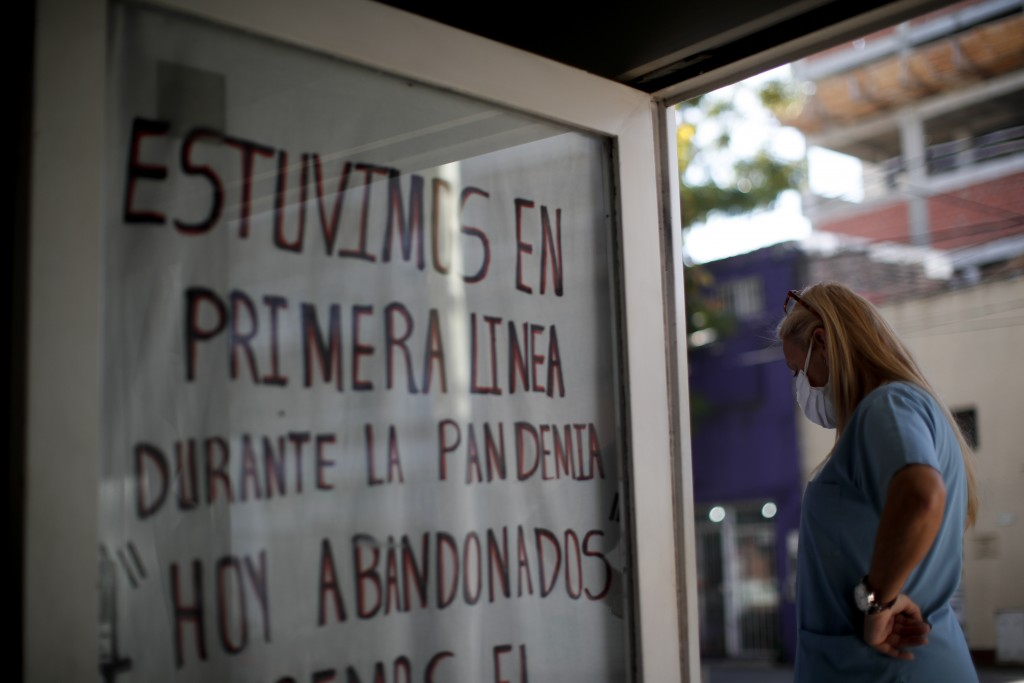 """Nurse Lidia Del Valle stands by a sign that says in Spanish """"We were on the front lines during the pandemic. Today, abandoned,"""" outside San Andres Cli..."""