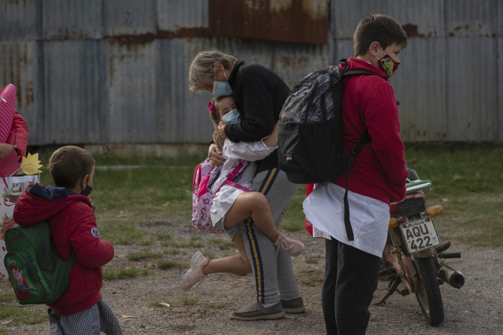 A student embraces a woman before entering school for the first time since it was closed due to the COVID-19 pandemic in Migues, Uruguay, Monday, May ...