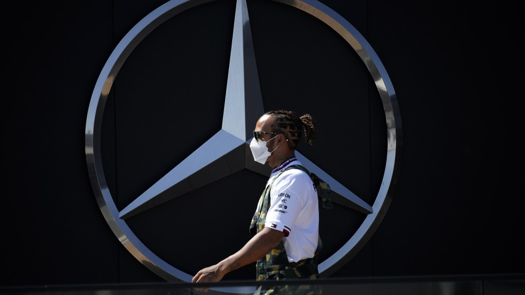 Mercedes driver Lewis Hamilton of Britain walks past a Mercedes logo in the paddock ahead of the Spanish Formula One Grand Prix at the Barcelona Catal...