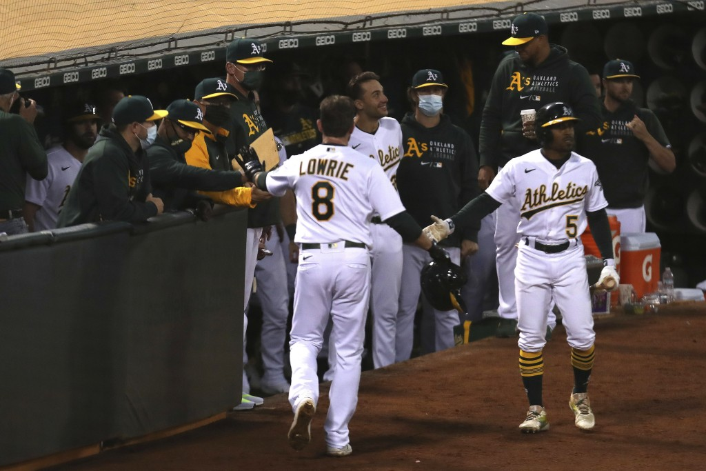Oakland Athletics' Jed Lowrie is congratulated by teammates after scoring on a single by Seth Brown against the Tampa Bay Rays during the seventh inni...