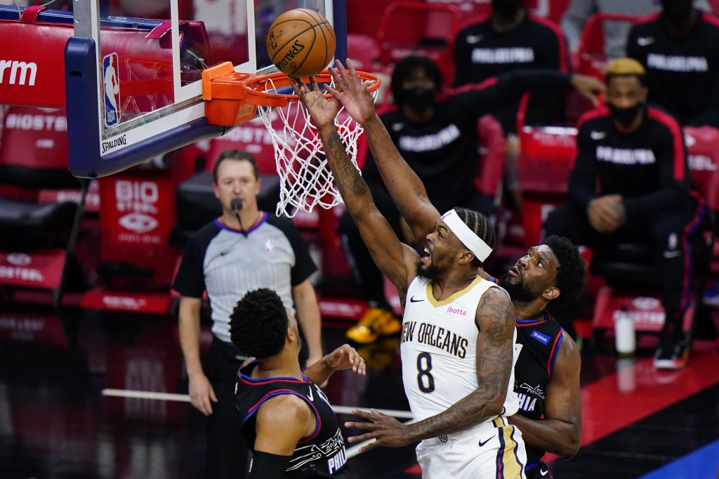 New Orleans Pelicans' Naji Marshall, center, goes up for a shot between Philadelphia 76ers' Joel Embiid, right, and Tobias Harris during the second ha...