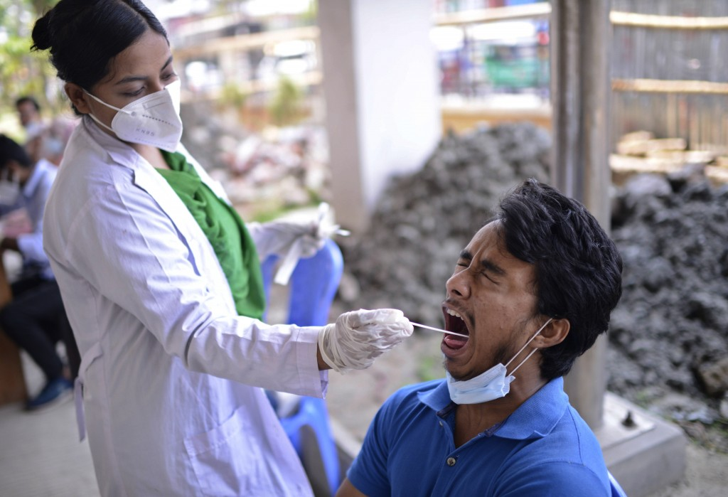 A Bangladeshi health worker takes a mouth swab sample of a man to test for COVID-19 in Dhaka, Bangladesh, Saturday, May 8, 2021. India's surge in coro...