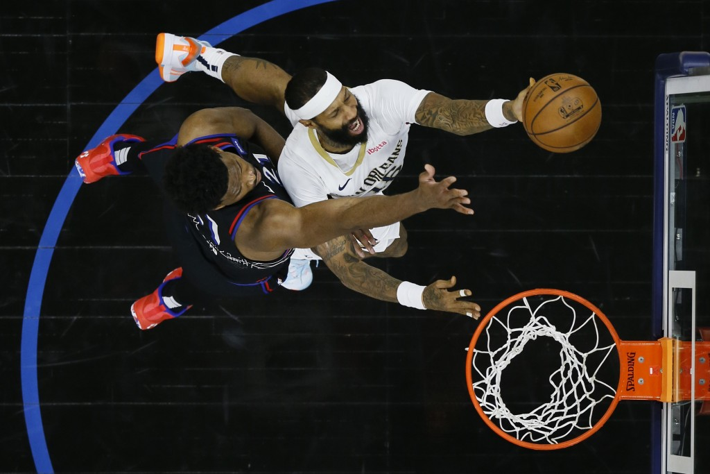 New Orleans Pelicans' James Johnson, right, goes up for a shot against Philadelphia 76ers' Joel Embiid during the second half of an NBA basketball gam...