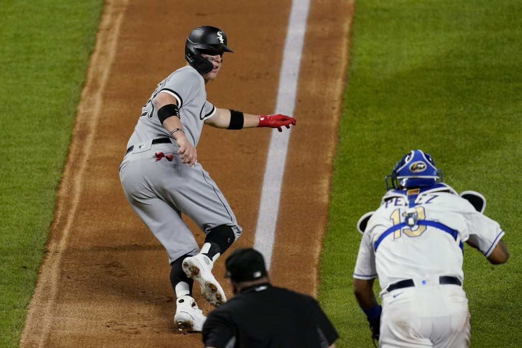 Kansas City Royals catcher Salvador Perez chases Chicago White Sox's Zack Collins back to third as Collins tried to score on a ball hit by Nick Madrig...