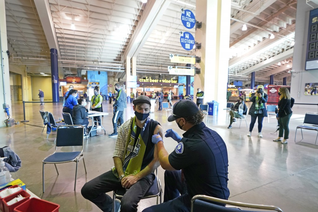 FILE - In this May 2, 2021, file photo, Austin Kennedy, left, a Seattle Sounders season ticket holder, gets the Johnson & Johnson COVID-19 vaccine at ...