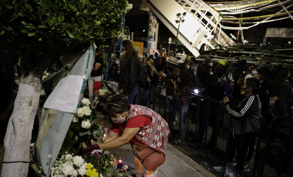 A woman places flowers at a makeshift altar during a protest demanding justice for the people who died in Monday's subway collapse, at the site of the...