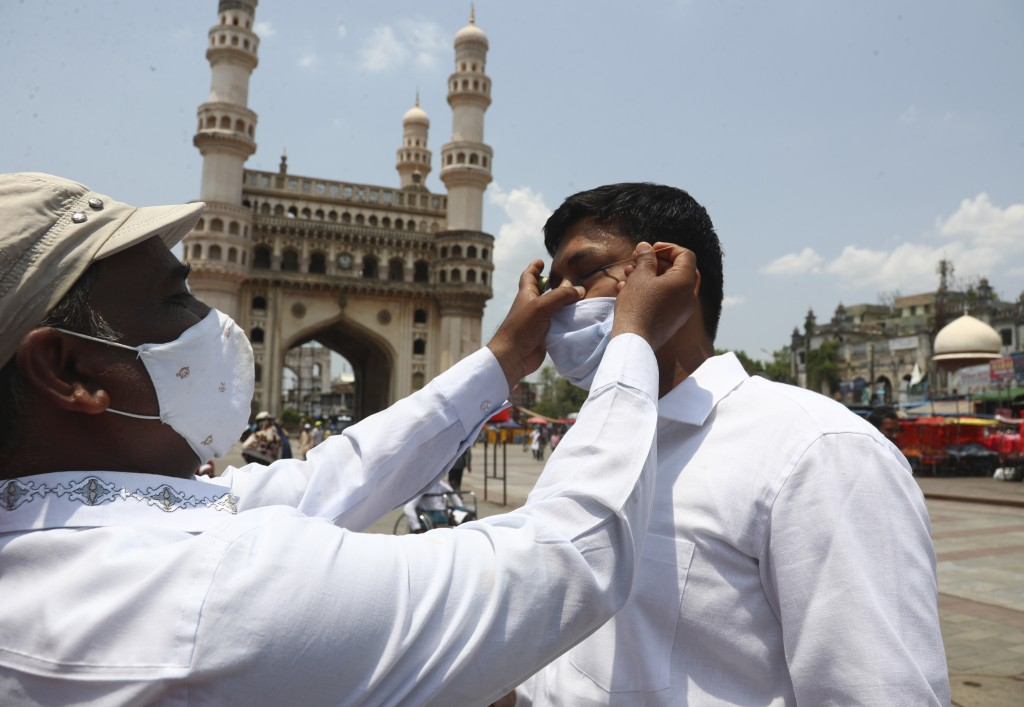 An Indian Muslim wearing face mask as a precaution against coronavirus gets his eyes lined with a black ointment called Surma, before offering last Fr...
