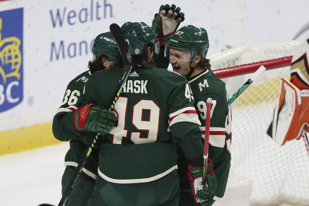 Minnesota Wild's Victor Rask (49) celebrates with teammates Mats Zuccarello (36) and Kirill Kaprizov (97) after scoring a goal against the Anaheim Duc...