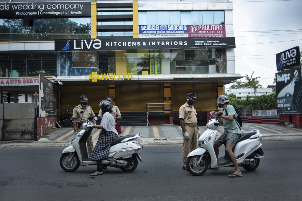 Policemen check the credentials of commuters during a lockdown imposed to curb the spread of coronavirus in Kochi, Kerala state, India, Saturday, May ...