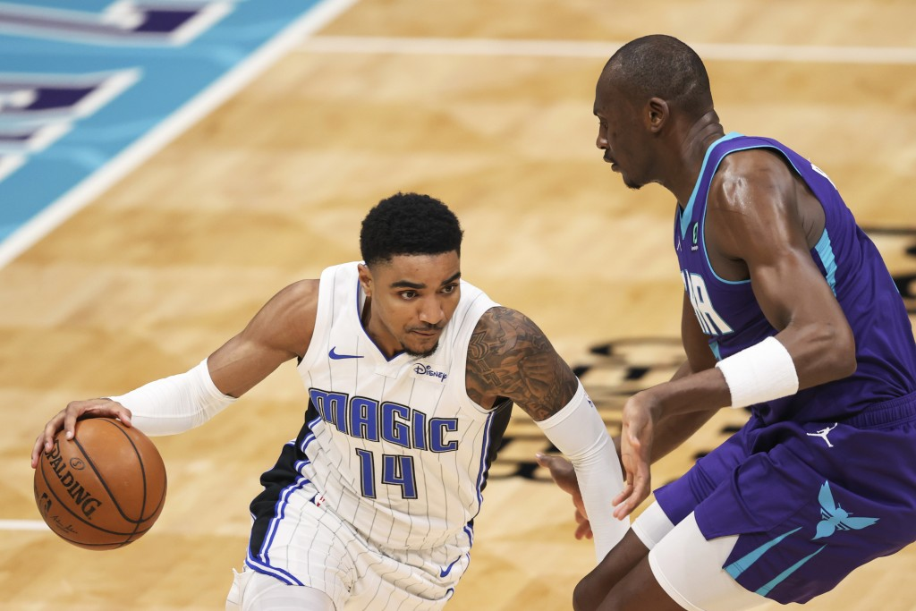 Orlando Magic guard Gary Harris (14) drives on Charlotte Hornets center Bismack Biyombo during the second half of an NBA basketball game in Charlotte,...