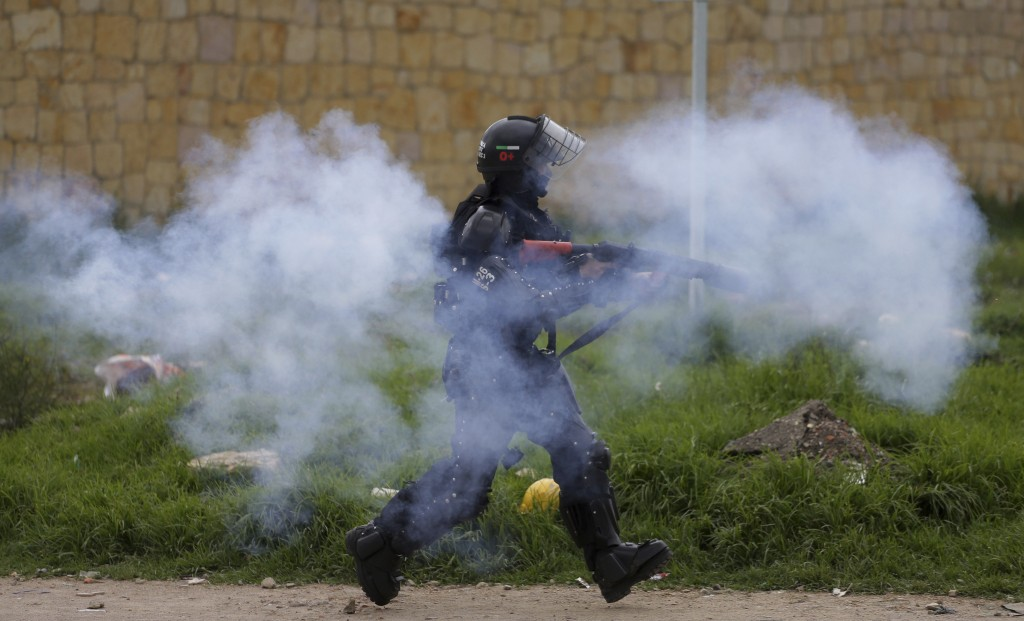 A police officer fires tear gas at anti-government protesters during clashes in Gachancipa, Colombia, Friday, May 7, 2021. The protests that began las...