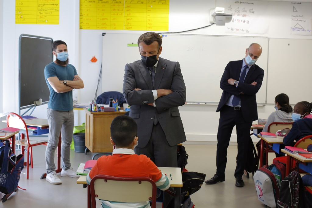 FILE - In this April, 26, 2021 file photo, French President Emmanuel Macron talks with a pupil during a visit with French Education, Youth and Sports ...