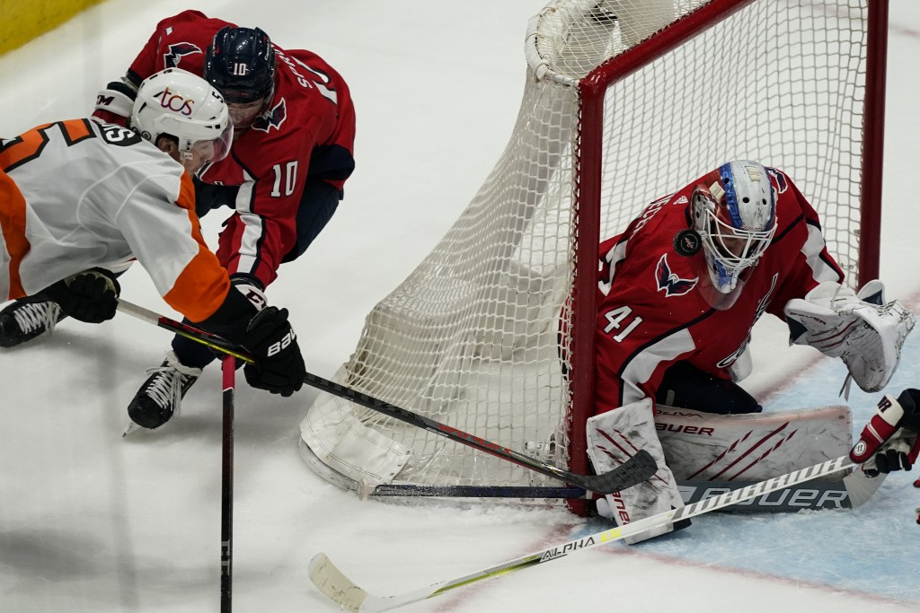 Philadelphia Flyers defenseman Philippe Myers (5) shoots as Washington Capitals right wing Daniel Sprong (10) defends with Washington Capitals goalten...