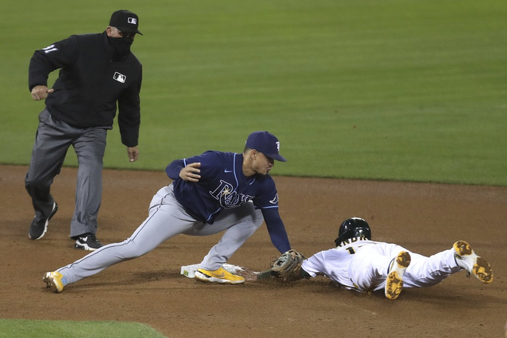 Oakland Athletics' Elvis Andrus, right, is tagged out by Tampa Bay Rays' Willy Adames on a steal attempt during the seventh inning of a baseball game ...