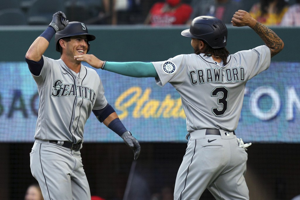 Seattle Mariners' Dylan Moore (25) celebrates his two-run home run with J.P. Crawford (3) during the second inning against the Texas Rangers in a base...