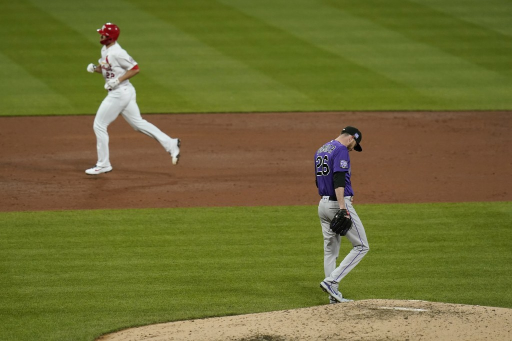 Colorado Rockies starting pitcher Austin Gomber (26) walks around the mound as St. Louis Cardinals' Jack Flaherty rounds the bases after hitting a sol...