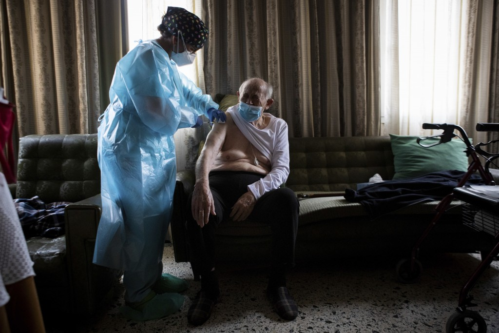 Nurse Pilar Rodríguez administers the COVID-19 vaccine to her patient Rafael Capo Frau, 92, at his home in the town of Sa Pobla on the Spanish Baleari...