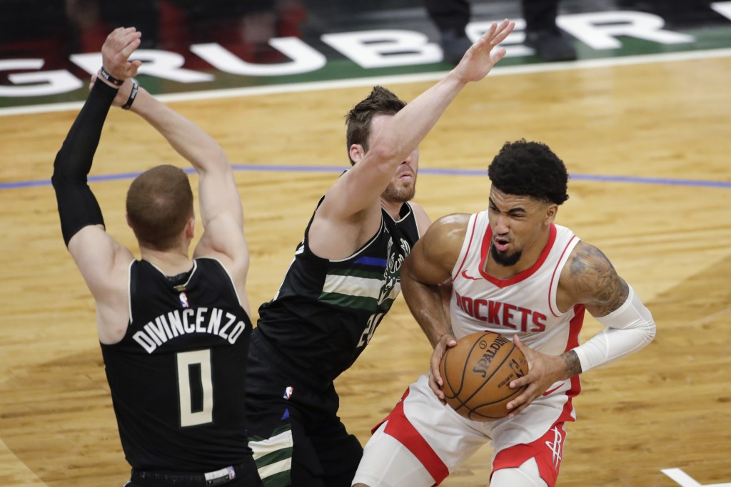 Houston Rockets' Kenyon Martin Jr., right, drives to the basket against Milwaukee Bucks' Pat Connaughton, middle, and Donte DiVincenzo, left, during t...