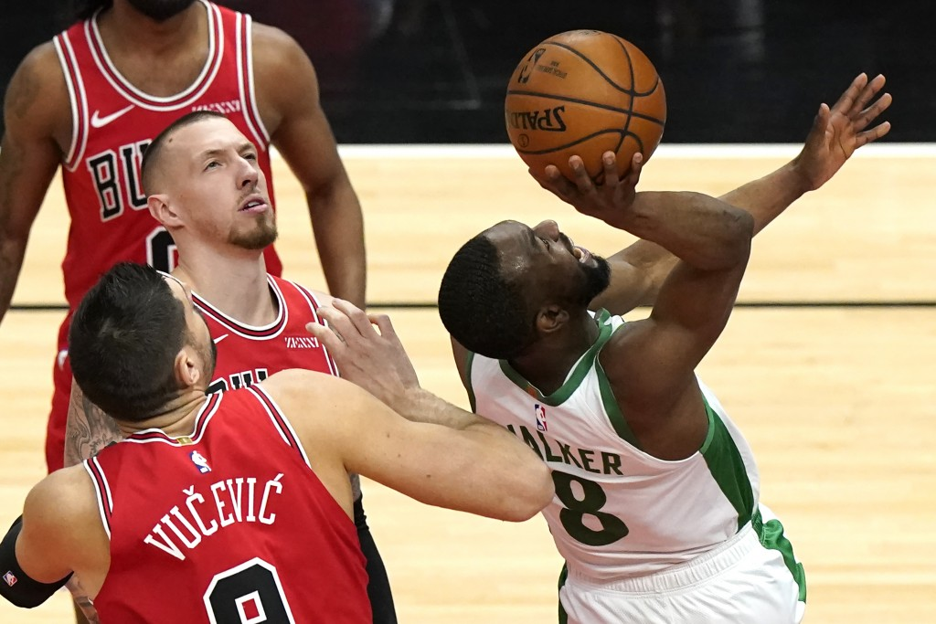 Boston Celtics guard Kemba Walker, right, shoots as Chicago Bulls center Nikola Vucevic and center Daniel Theis watch the ball during the first half o...