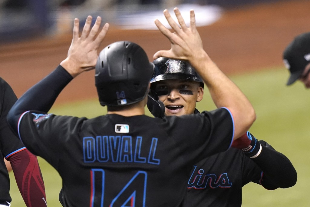 Miami Marlins' Isan Diaz, right, is met by Adam Duvall (14) at the plate after hitting a grand slam during the third inning of a baseball game against...