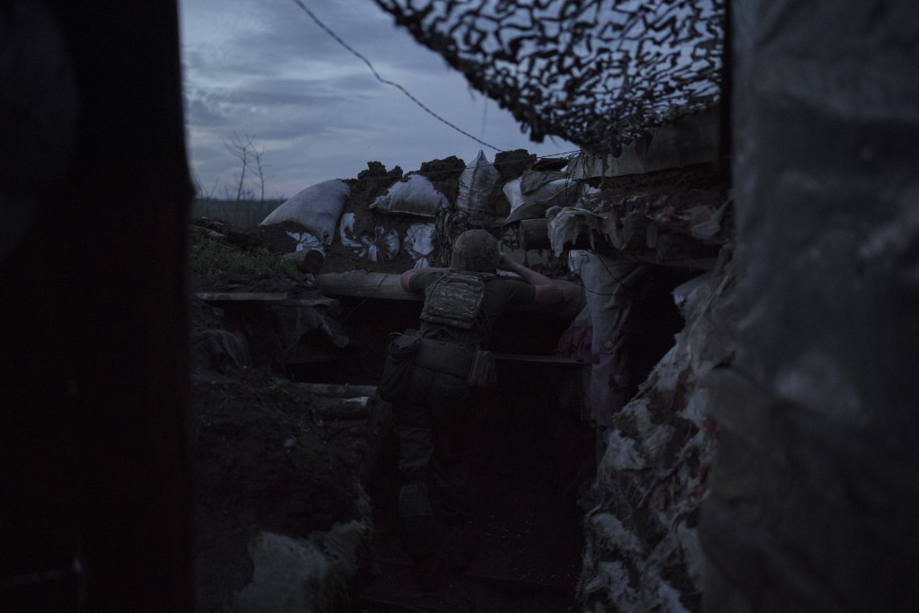 A Ukrainian soldier looks through his binoculars at dusk in a fighting position on the line of separation from pro-Russian rebels near Toretsk, easter...