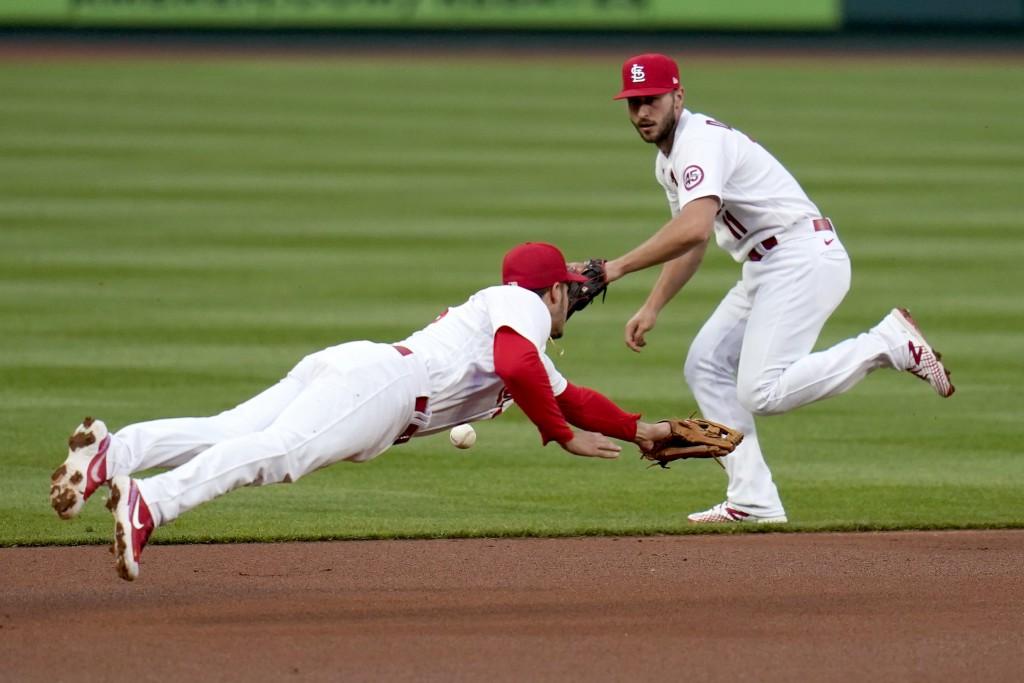 St. Louis Cardinals third baseman Nolan Arenado, left, dives but is unable to reach a single by Colorado Rockies' Garrett Hampson as Cardinals shortst...